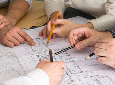Home remodeling contractors working with homeowners over an interior design plan