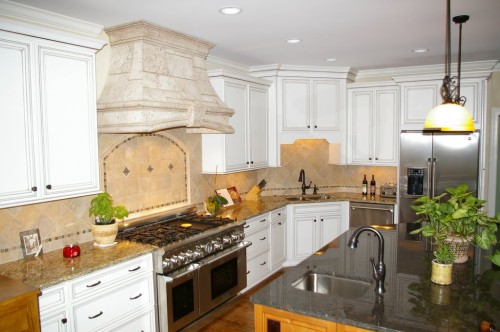 Photo of completed major kitchen remodel project showing large gas range, custom tile backsplash and new granite island with updated sink faucet