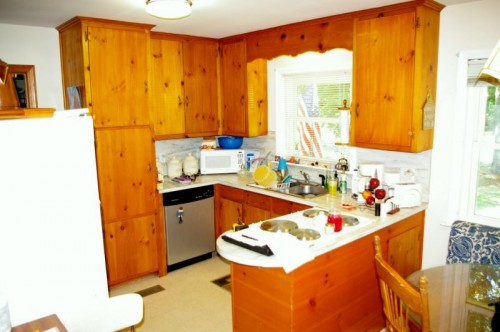 Before kitchen remodel with view of outdated appliances, awkward countertop and limited space