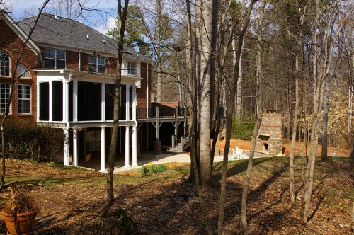 After home addition photo of deck expansion, screened porch addition and outdoor fireplace