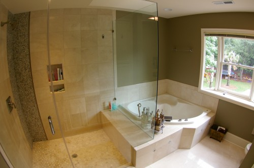 After bathroom renovation with view of new walk-in tile shower and tub