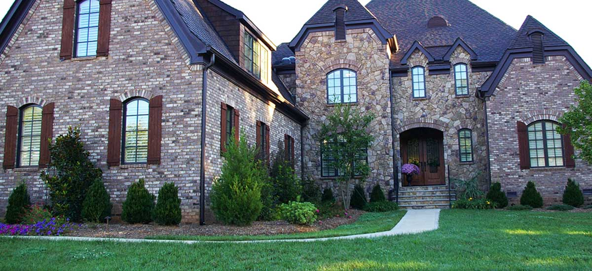 Front facing photo of a custom home builder's newly completed Tuscan country manor in the greater Charlotte area