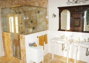 New and beautiful bathroom with view of his and her vanities and custom walk-in tile shower