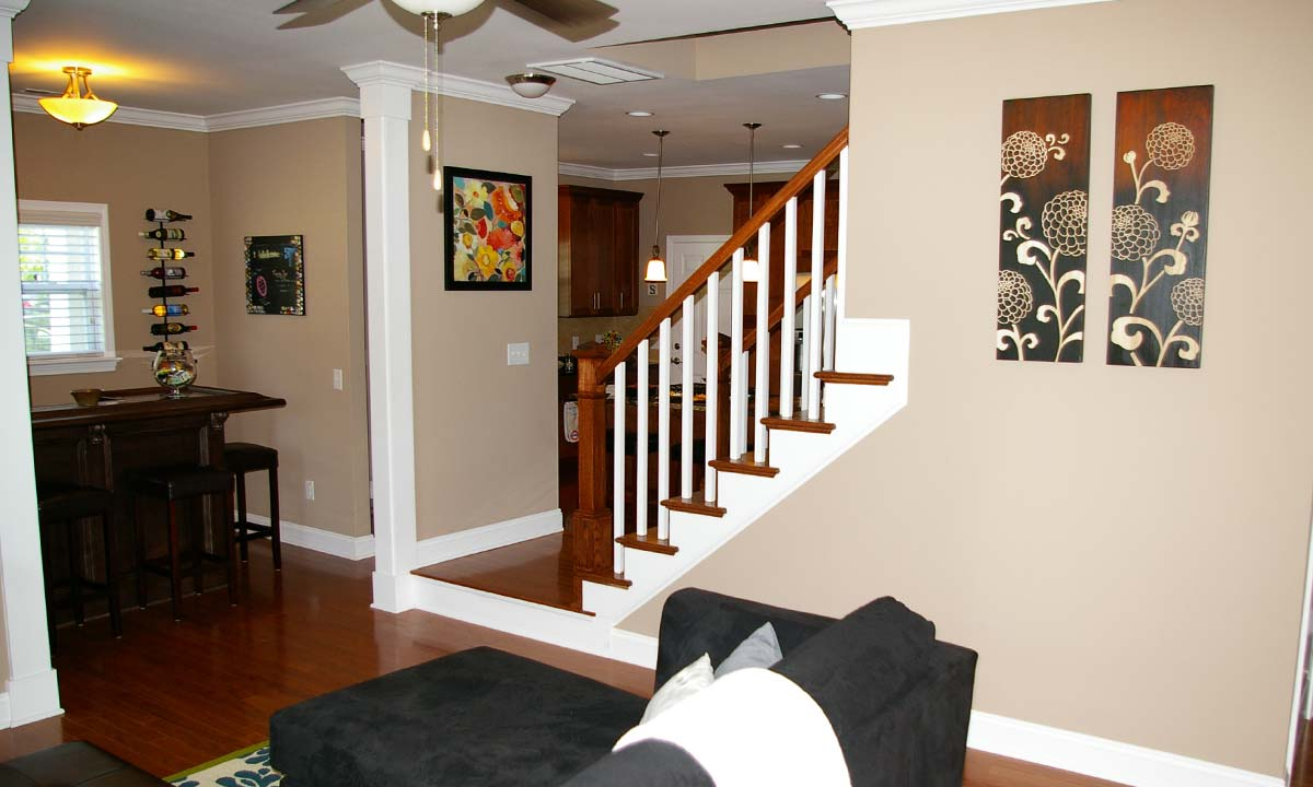 Picture showing the benefits of a custom layout by showing the home's bar adjacent to staircase