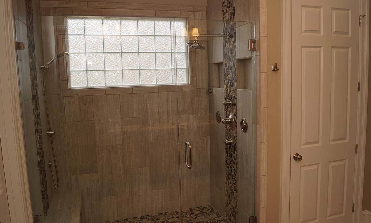 New shower with beautiful tilework and frameless glass complete the high-end look