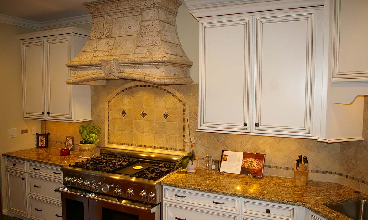 """After"" photo showing a different angle of the granite countertops and tile backsplash"