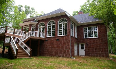 Exterior photo showing the new home with large two-story addition, deck and outside staircase