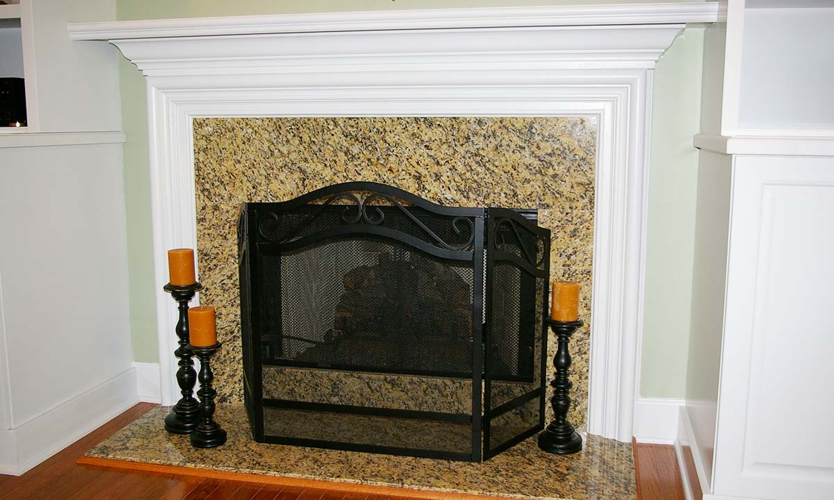 New granite fireplace with colonial style base molding