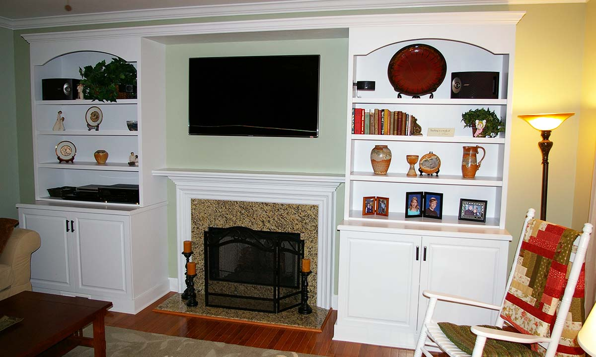 New bookcases beautifully frame the new fireplace after this family room makeover