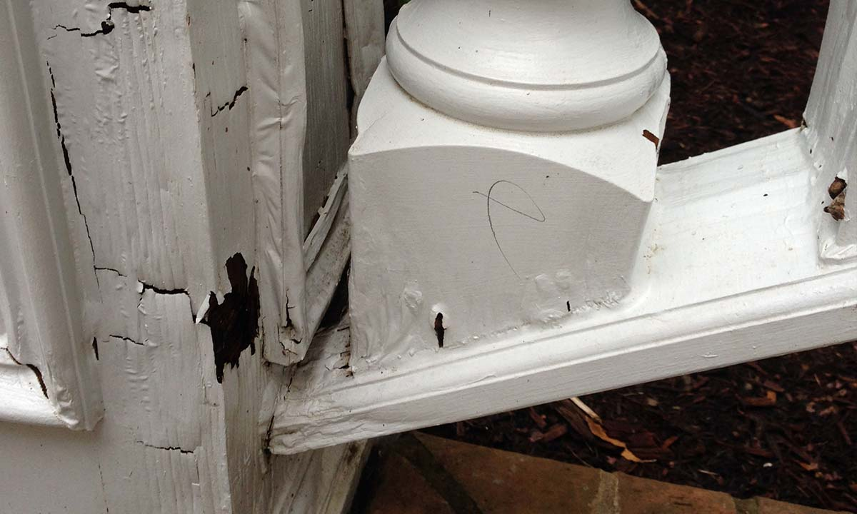Close-up of front porch railing damage and wood rot