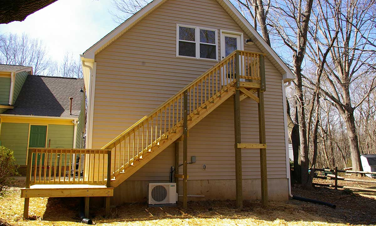 Back-facing photo of completed garage addition with deck and staircase leading to bonus room