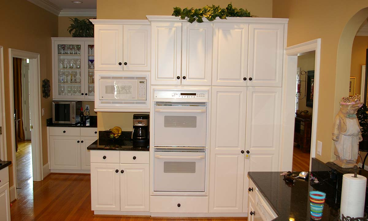 Dated and peeling white thermofoil cabinets before the remodel