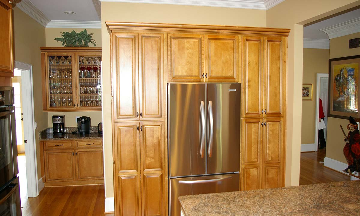 New kitchen cabinets frame the refrigerator and have ample storage