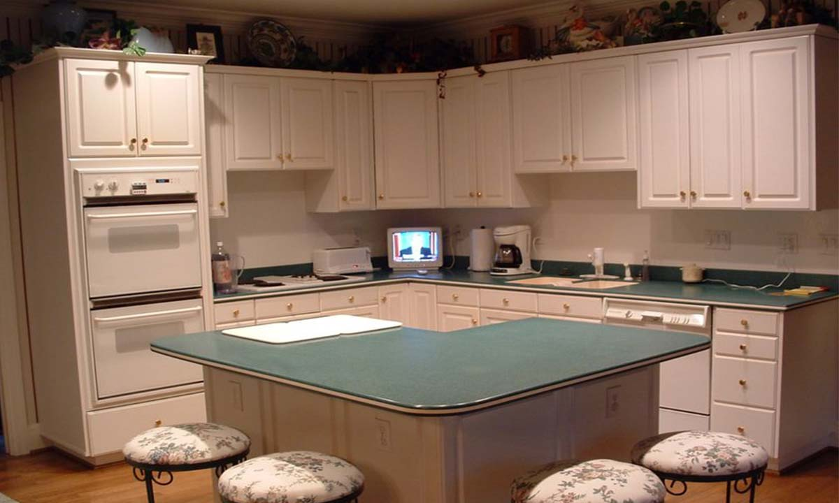 Before picture of kitchen redesign with L shaped island and outdated countertop