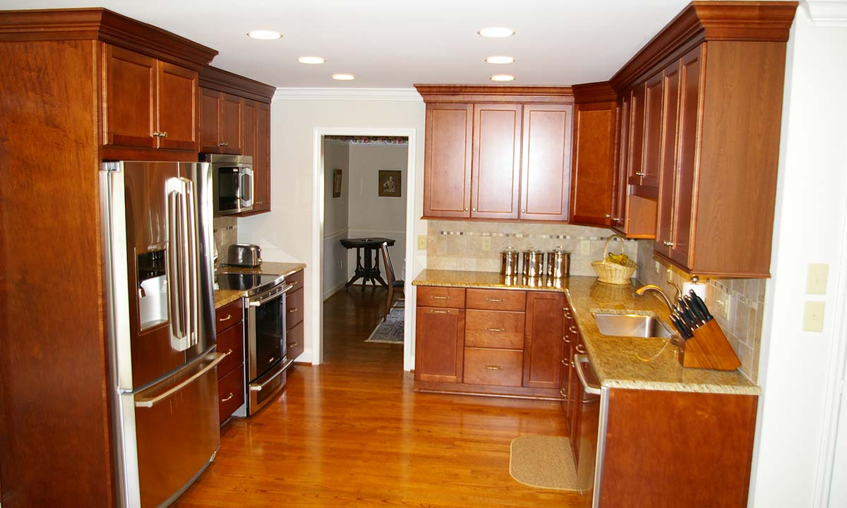 After kitchen renovation with view of stainless steel appliances, overhead lighting and no more dropped soffit