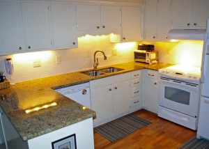 """After"" picture of this kitchen renovation with granite surface and high-arch faucet"