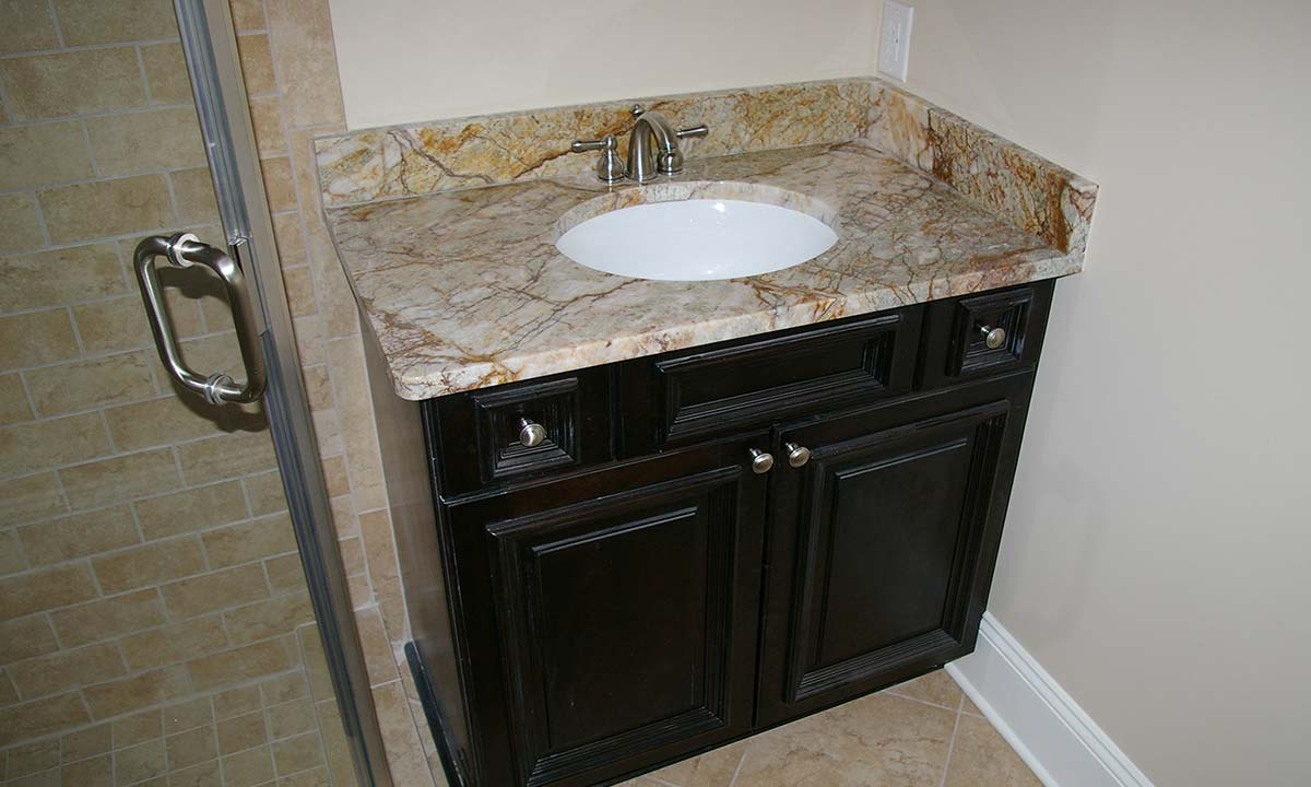 Picture of new full bathroom with granite sink and angled walk-in shower