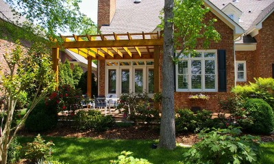 Photo of the new rough-sawn, cedar-beamed pergola anchored to house