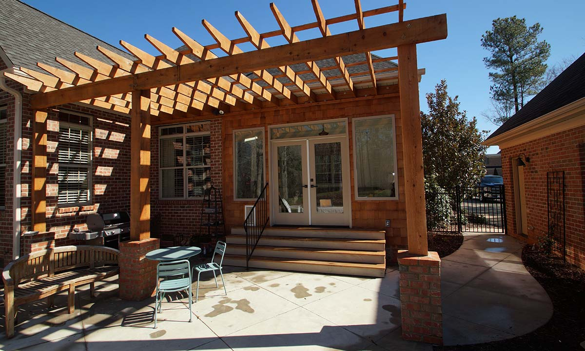 New pergola tied to existing structure and outdoor gathering area