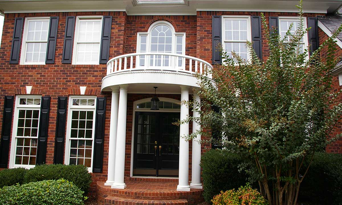 After photo of portico repair and renovation with new custom-manufactured curved white vinyl railing installed
