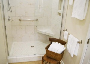 New and larger walk-in tile shower with grab bar for safety