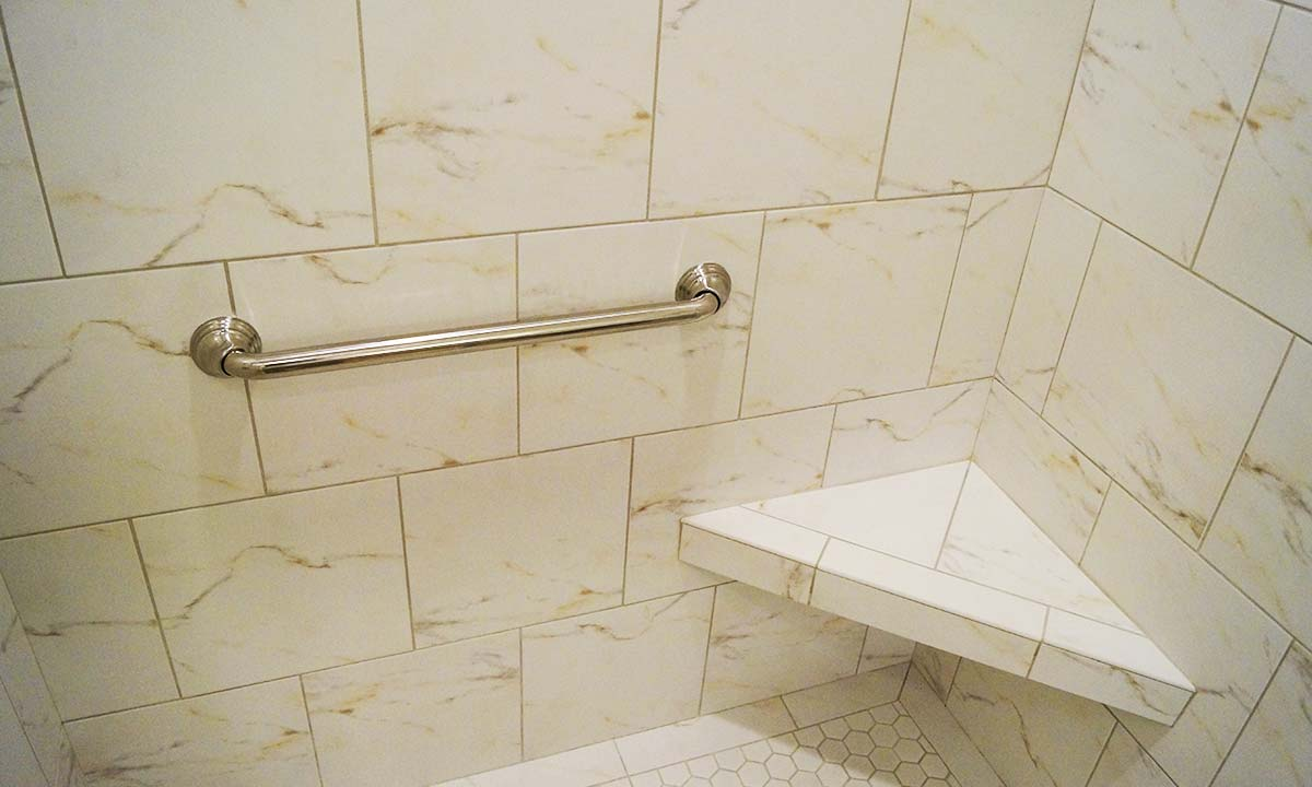 Photo of safety grab bar in new tiled shower and tile shower seat