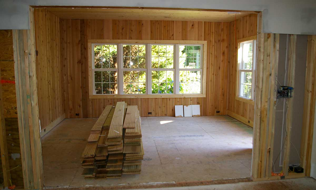 Interior view of the sunroom being built with reclaimed hardwood flooring for seamless flow between house and sunroom