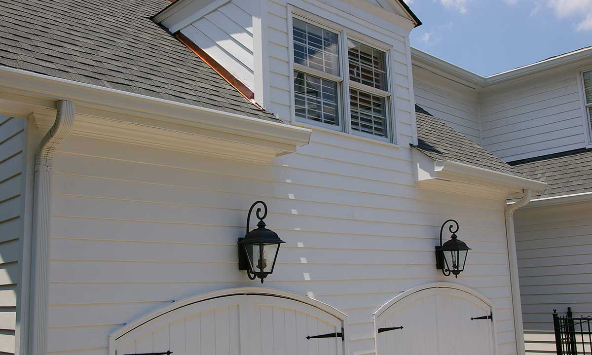 After dormer repair photo showing redesigned and replaced dormer siding and trim and new copper step and counter flashing
