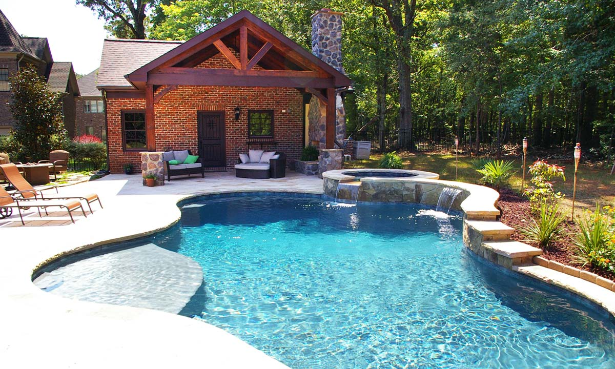 Picture of a newly finished pool house addition and custom pool with waterfall.