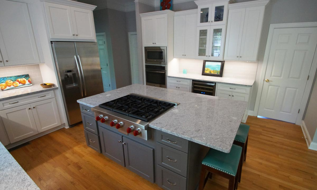 gray island with gray and white granite countertops
