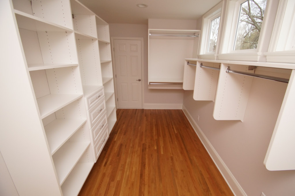 walk in closet with hardwood floors and custom shelves and drawers