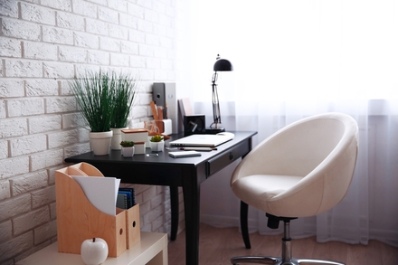 white brick wall with wooden desk and white desk chair